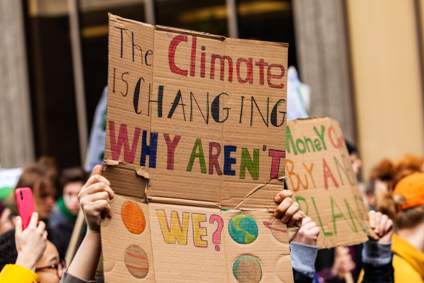 Homemade sign at environmental rally. A colorful cardboard placard is viewed close up, saying the climate is changing, why aren't we, in the hands of ecological activists as they protest in the city