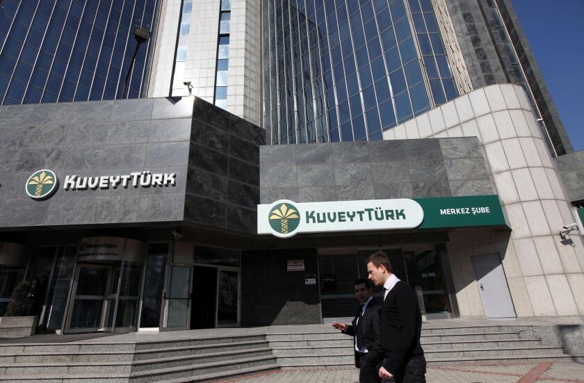 People walk past the Kuveyt Turk head office in Istanbul February 21, 2012. Turkey's government plans its first-ever issue of Islamic bonds this year, overcoming sensitivities about Islamic finance in the secular republic as it seeks to tap a rich pool of