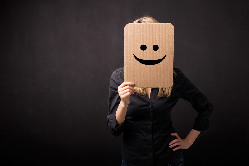 Woman holding cardboard with smiley in front of her face