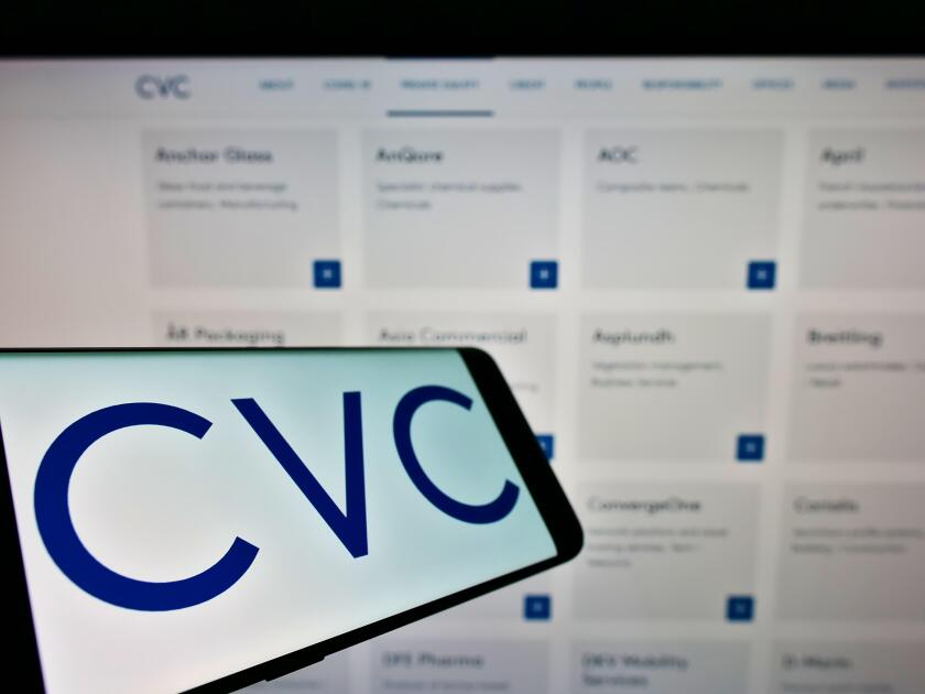 Smartphone with logo of private equity company CVC Capital Partners on screen in front of business website. Focus on center-left of phone display.