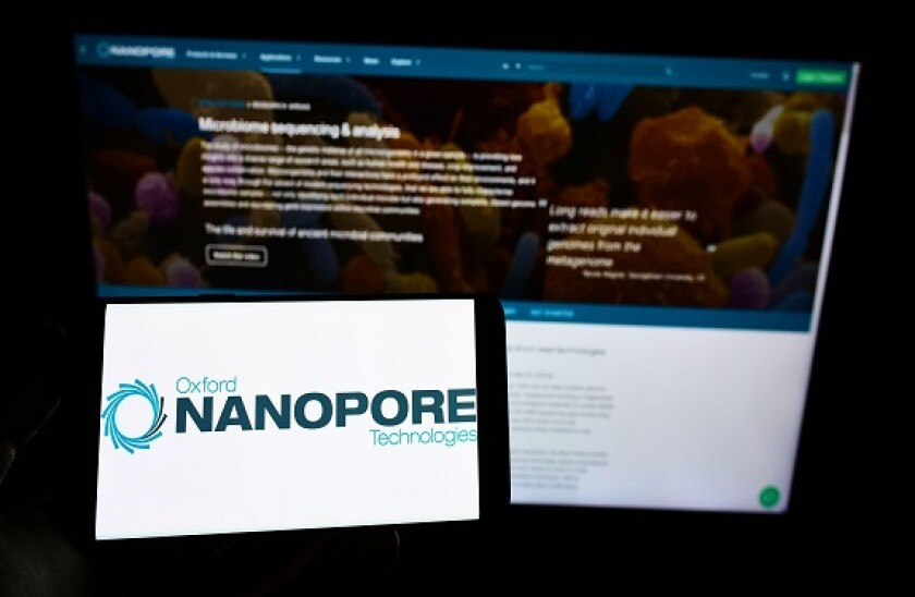 Person holding smartphone with logo of company Oxford Nanopore Technologies Limited on screen in front of website. Focus on phone display.