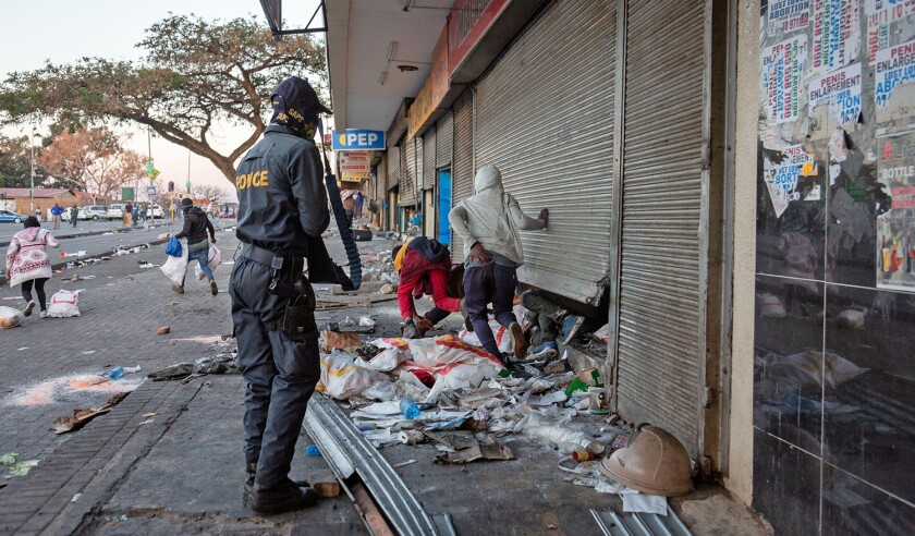 (210712) -- JOHANNESBURG, July 12, 2021 (Xinhua) -- A police officer deals with protesters looting a shop in Johannesburg, South Africa, on July 12, 2021. Soldiers have been deployed in KwaZulu-Natal and Gauteng provinces to deal with violent protests and