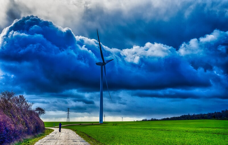 Silhouette of man on path with wind turbine and stormy sky, West Yorkshire, England, Britain