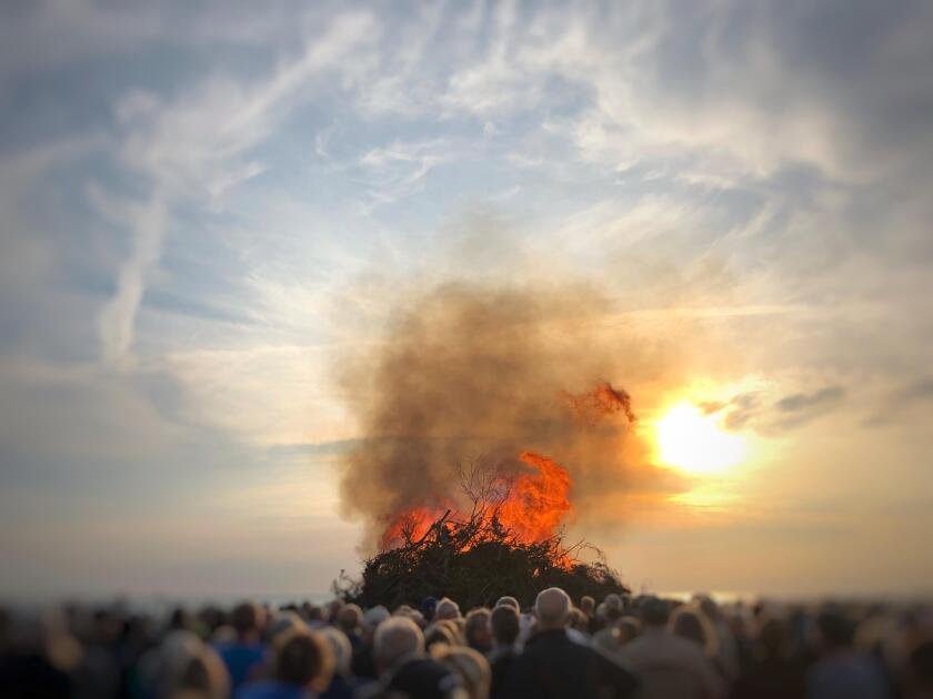 People watching a bonfire on the beach at midsummer, Fanoe, Denmark