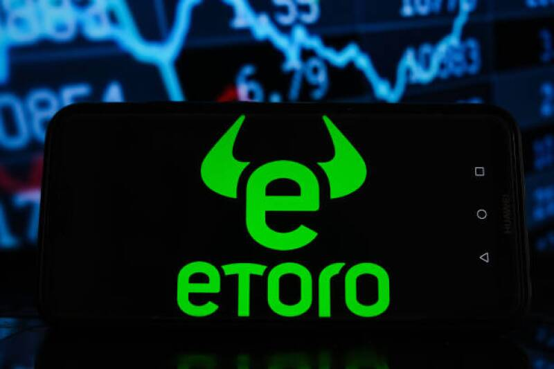 In this photo illustration an eToro logo seen displayed on a...