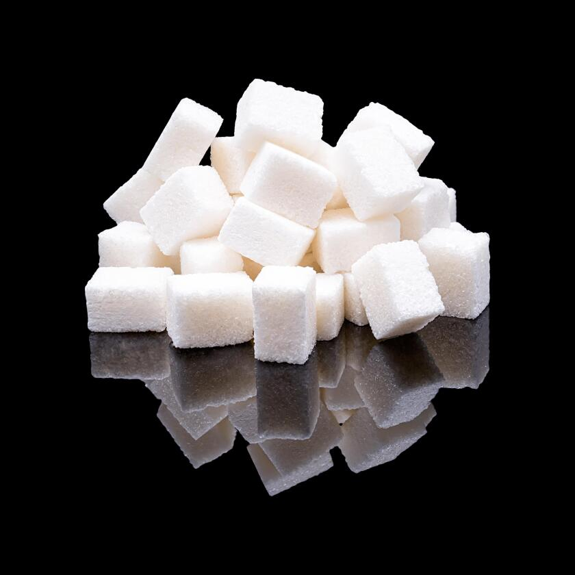 Cubes of white sugar from sugar beet with a real reflection on a black glossy background