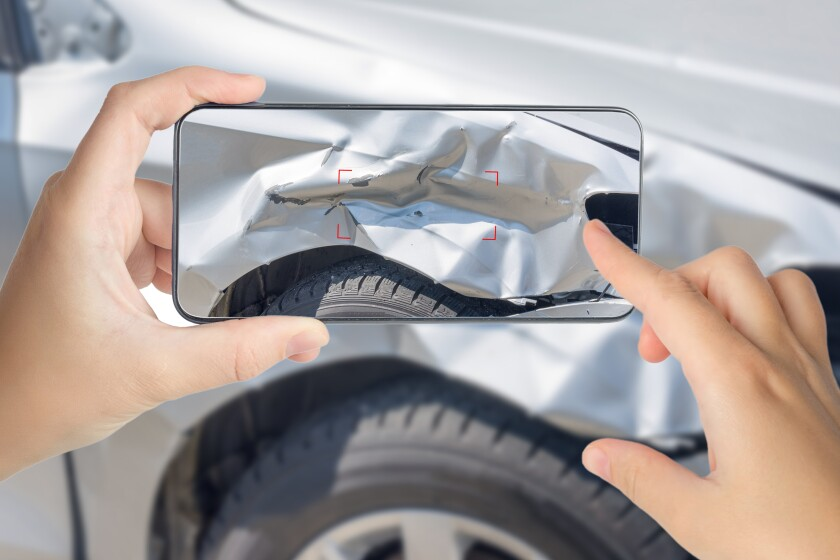 A girl takes pictures on a smartphone of car damage at the scene of an accident for insurance compensation.