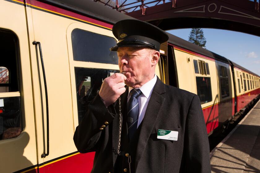 UK, England, Yorkshire, Goathland, North Yorkshire Moors Railway guard Peter Glenn, blowing whistle