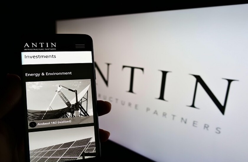 Person holding cellphone with webpage of investment company Antin Infrastructure Partners on screen with logo. Focus on center of phone display.