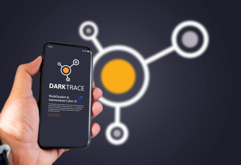 Cambridge, UK, May 2021: A hand holding a phone with the Darktrace company logo on the screen. Darktrace is an AI company that specialises in cyber de