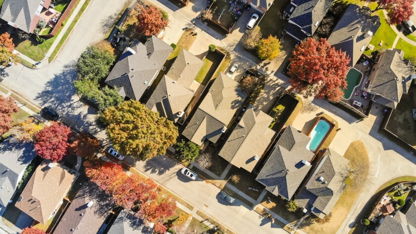 Aerial view urban subdivision houses with pool and autumn leaves near Dallas