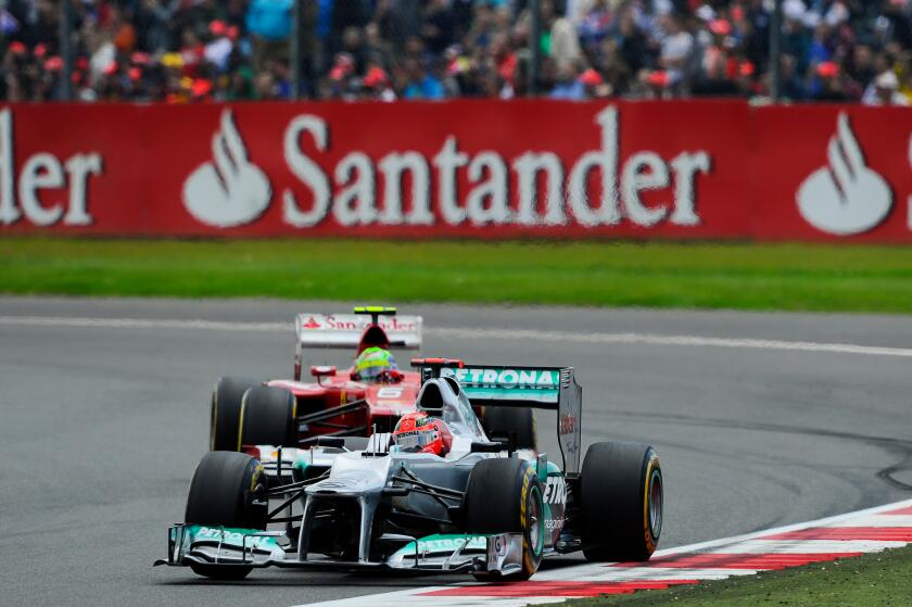 08.07.2012 Towcester, England. Michael Schumacher of Germany and Mercedes AMG Petronas F1 Team and Felipe Massa of Brazil and Scuderia Ferrari in action during the Race at the Santander British Grand Prix, Round 9 of the 2012 FIA Formula 1 World Champions