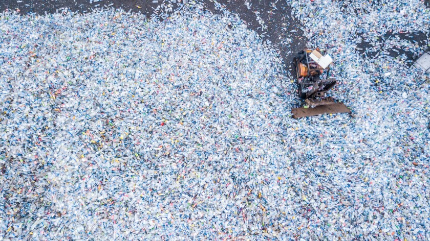Aerial top view  large garbage bottle pile background, Garbage pile in trash dump, Waste from household, Bottle waste disposal in dumping site, excavator machine is working on a mountain garbage.