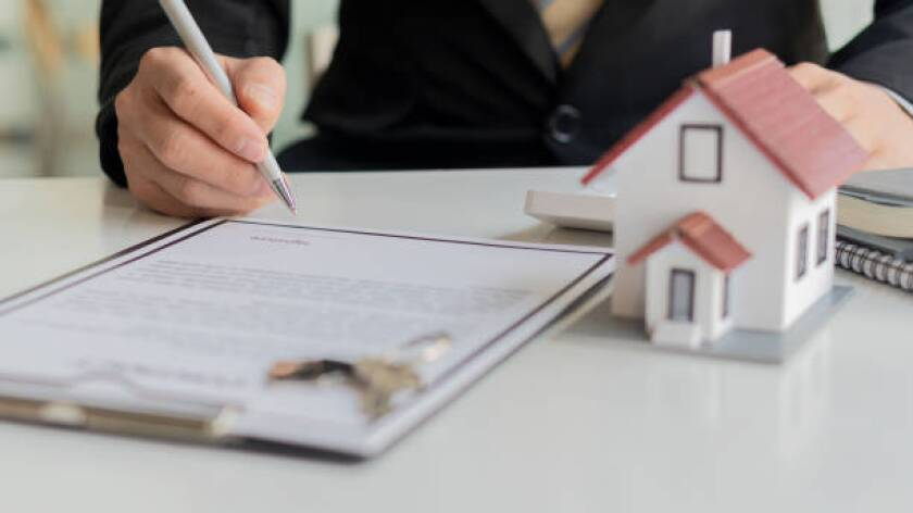 Businessman or home sales representative working with contract documents and calculators with laptops. To calculate interest, taxes and profits for real estate investments and home purchases.