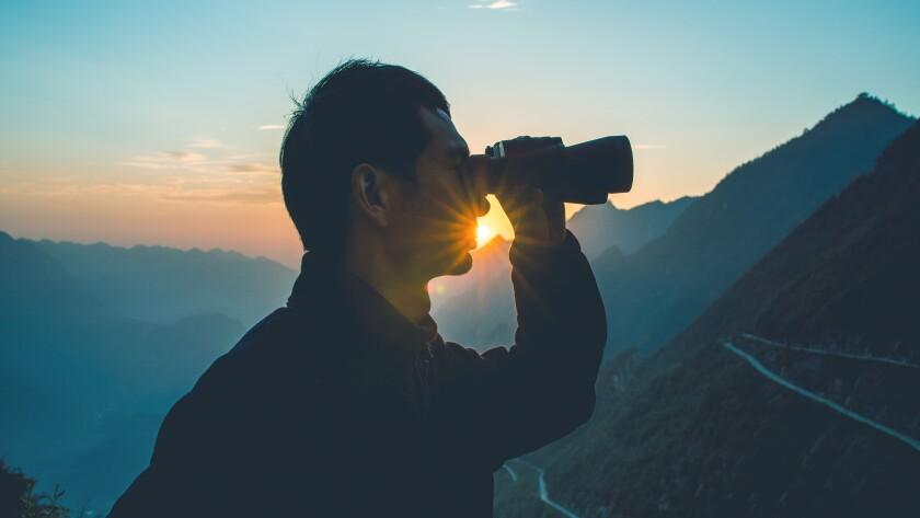 Man looks through binoculars in mountain