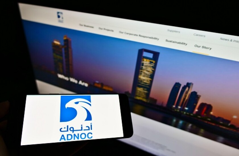 Person holding smartphone with logo of Abu Dhabi National Oil Company (ADNOC) on screen in front of website. Focus on phone display. Unmodified photo.
