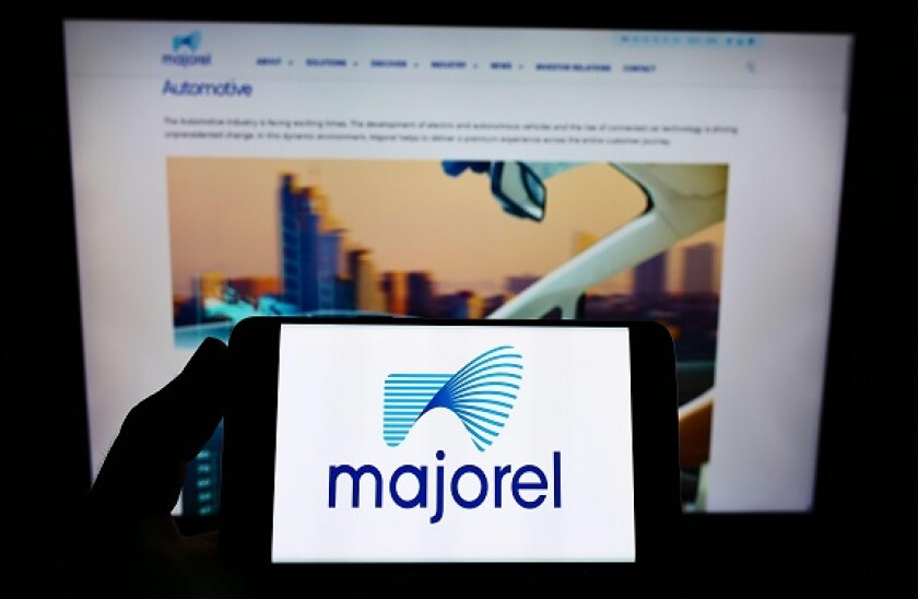 Person holding smartphone with logo of service company Majorel Group Luxembourg S.A. on screen in front of website. Focus on phone display.