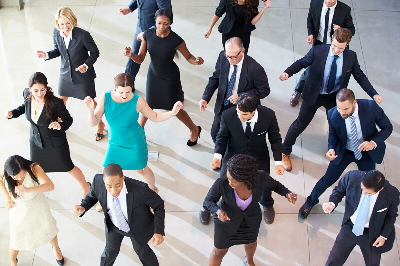 Overhead of businesspeople dancing in an office lobby