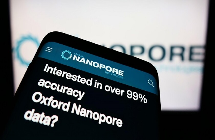 Smartphone with website of company Oxford Nanopore Technologies Limited on screen in front of business logo. Focus on top-left of phone display.