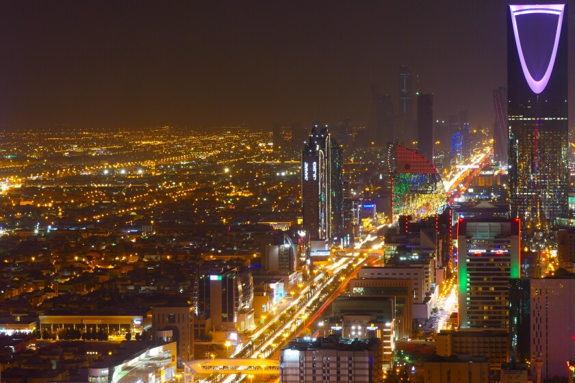 Panorama view to the skyline of Riyadh by night, with the Kingdom centre in the background and light purple lighting, the capital of Saudi Arabia