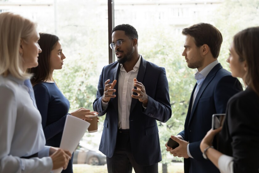 Confident African male leader telling diverse colleagues about new project