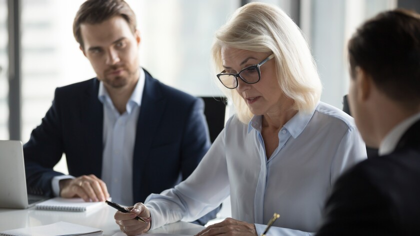 Concentrated aged businesswoman checking agreement before signing