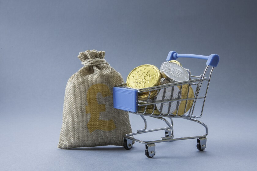 Supermarket shopping trolley full of UK currency, cash, coins and money representing consumer spending with copy space