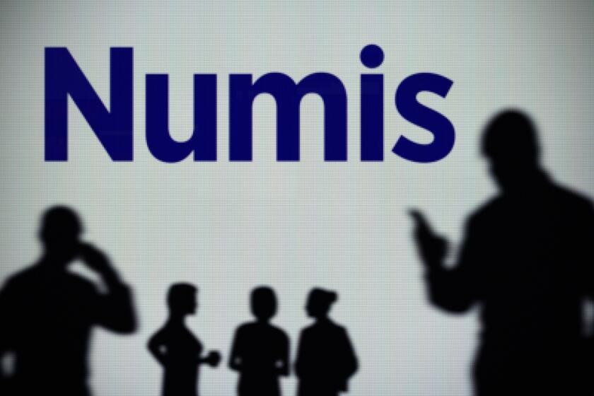 The Numis Securities logo is seen on an LED screen in the background while a silhouetted person uses a smartphone (Editorial use only)