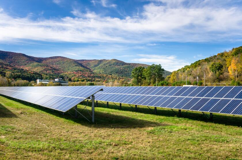 Rows of solar panels in a field in the Mountains on a sunny autumn day