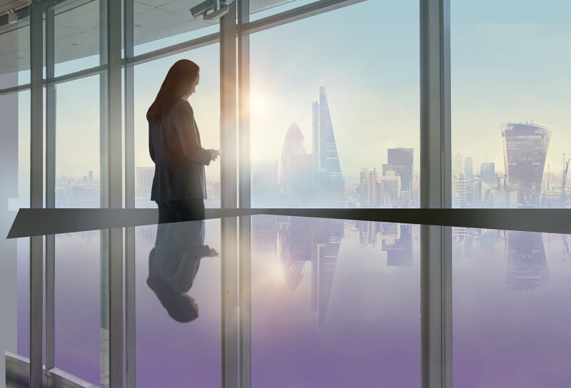 Young woman standing next to the office window with beautiful City of London view and reading message on the phone