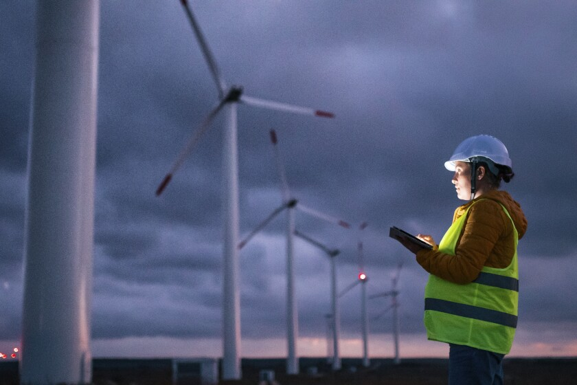 Renewable Energy Systems. Electricity Maintenance Engineer working on the field at a Wind Turbine Power station at dusk with a moody sky behind. Blurred motion.
