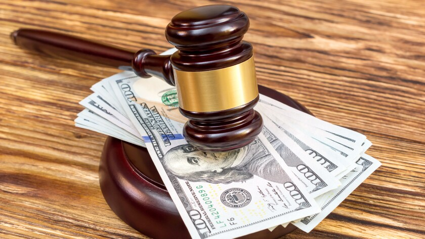 Judge's gavel and stand with US dollar bills on the wooden table.