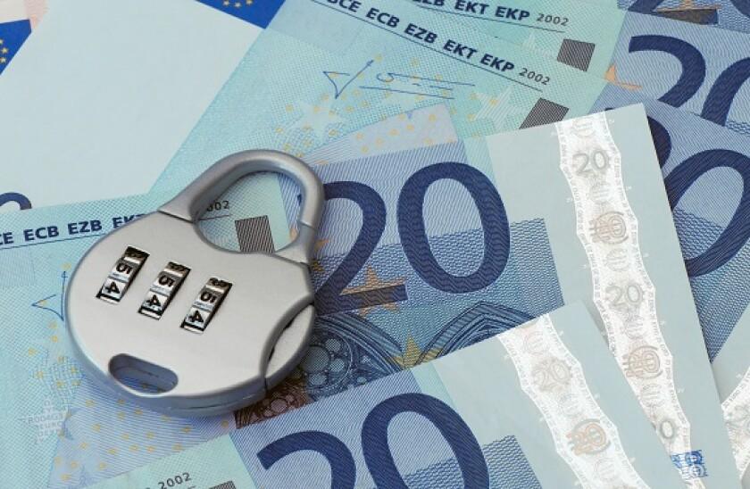 Combination padlock rests on Twenty Euro banknotes