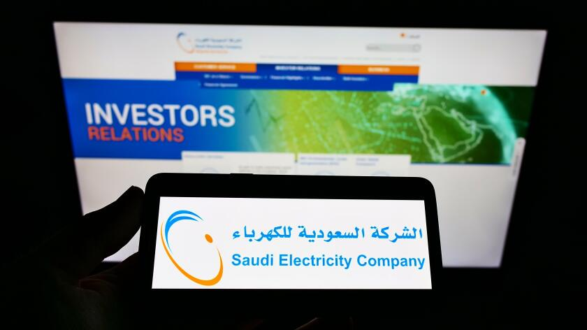 Person holding cellphone with logo of electric utility business Saudi Electricity Company (SEC) on screen with webpage. Focus on phone display.