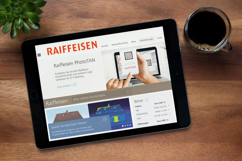 The website of the Swiss bank, Raiffeisen, is seen on an iPad tablet, resting on a wooden (Editorial use only).