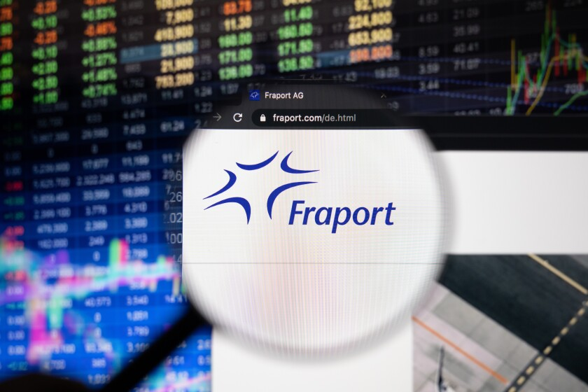 Fraport company logo on a website with blurry stock market developments in the background, seen on a computer screen through a magnifying glass