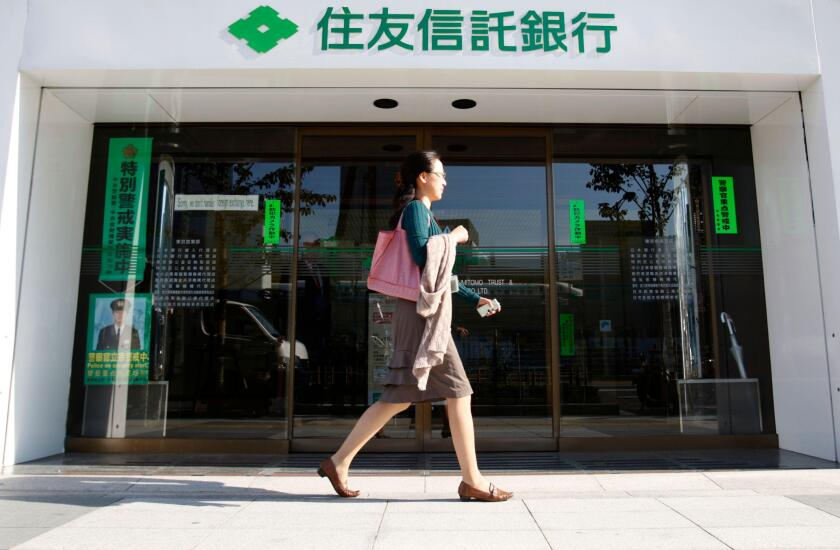 A woman walks past a branch of Sumitomo Trust and Banking Co in Tokyo November 6, 2009. Sumitomo Trust and Banking Co and Chuo Mitsui Trust Holdings Inc said they plan to merge, creating Japan's largest trust bank with scale to better compete in a crowded