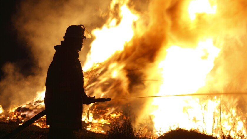 Firefighter Holding Hose Pointing Water Stream onto Fire