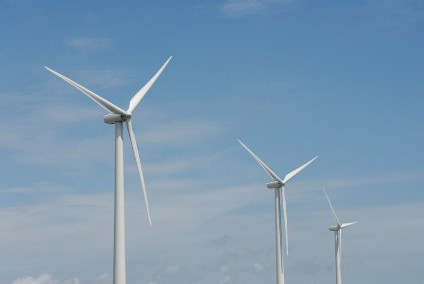 """Three wind turbines, close-up of blades, against blue sky. Wind power """"wind farm"""" turbines alternative energy, renwable energy."""