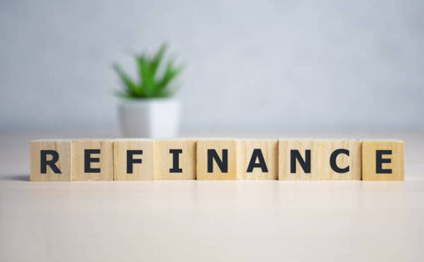 focus on wooden blocks with letters making Refinance text.