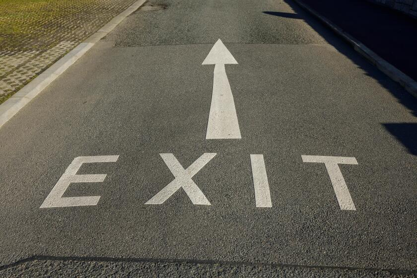 An Exit sign and arrow painted on a road in the UK
