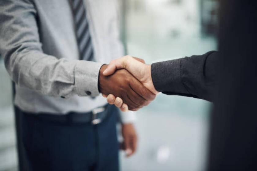 Shot of two unrecognisable businessmen shaking hands in a modern office