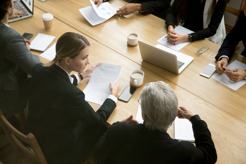 Negotiations concept, different businesspeople discussing deal details at group meeting