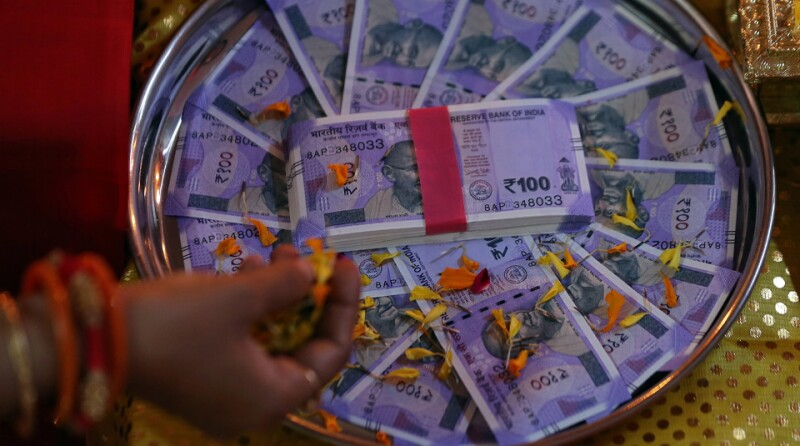 A woman puts flower petals on the new 100 Indian rupee notes as she prays as part of a ritual during Dhanteras, a Hindu festival associated with Lakshmi, the goddess of wealth, in Ahmedabad