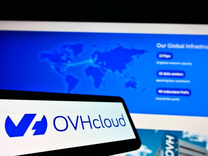 Mobile phone with logo of French cloud computing provider OVH Groupe SAS on screen in front of website. Focus on center-left of phone display.