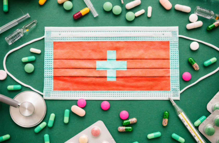Surgical mask with Swiss flag design, surrounded by pills, on a green surface