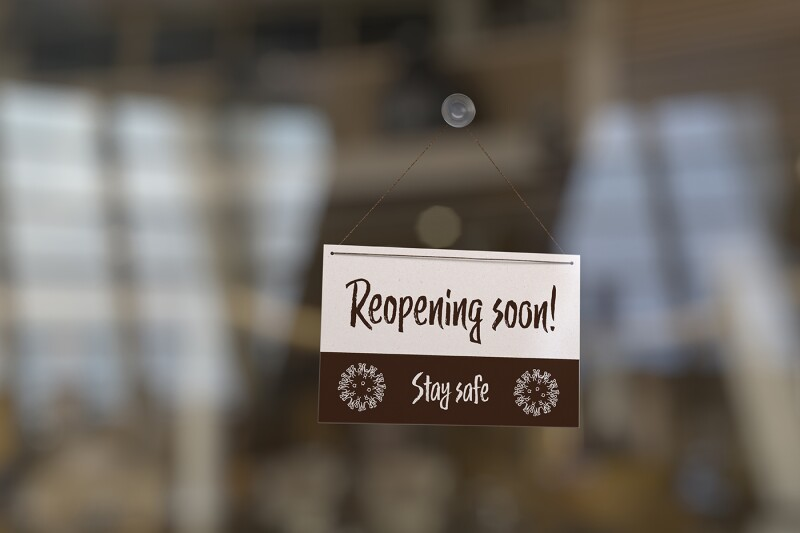 """Reopening the economy after corona virus concept: A sign on a restaurant or shop door with the text """"Reopening soon"""" and """"Stay safe""""."""