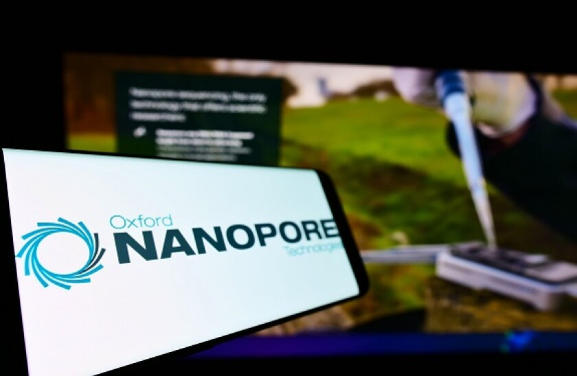 Cellphone with logo of company Oxford Nanopore Technologies Limited on screen in front of business webpage. Focus on left of phone display.