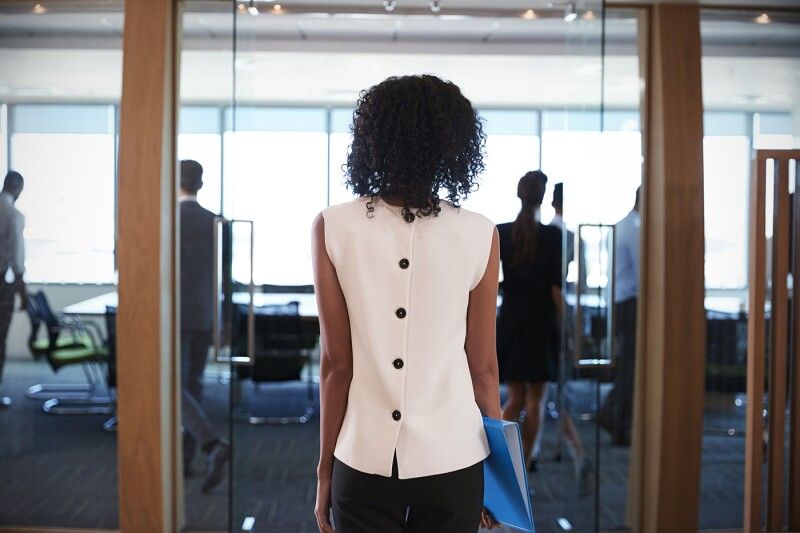 Rear View Of Businesswoman Entering Boardroom For Meeting