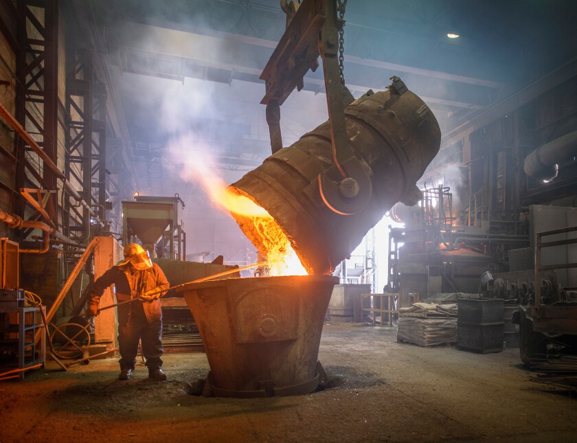 Steel worker and buckets of molten metal in steel foundry